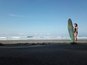Woman standing on the beach holding longboard surfboard
